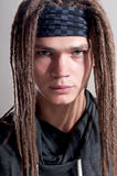 Young stylish guy with dreadlocks. Young stylish guy with dreadlocks over gray background Royalty Free Stock Image