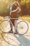 Young stylish guy with girl and the bicycle outdoors Royalty Free Stock Photography