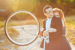 Young stylish guy with girl and the bicycle outdoors Stock Image