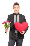 A young stylish guy holding a bunch of flowers and heart Stock Image
