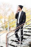 A young stylish guy with a pensive look is on the steps. Outdoors. Royalty Free Stock Photos
