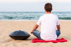 Young stylish guy sitting on the sand beach near handpan or hang with sea On Background. The Hang is traditional ethnic Royalty Free Stock Photo