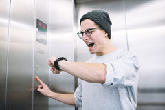 Young stylish guy standing in elevator. And pressing button to go up. Anxious boy is checking his time on his watch and sees he is late. He starts to panic Royalty Free Stock Photo