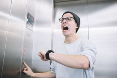 Young stylish guy standing in elevator. And sreaming in a despair, because he realised he had missed one of the most important moments in his life. He is crying Royalty Free Stock Photos