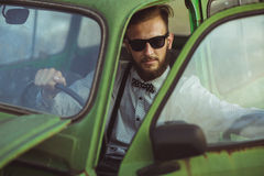 Young stylish handsome man, wearing shirt and sunglasses, drivin Royalty Free Stock Image