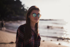 Young stylish happy hipster woman traveling around the world wearing aviator sunglasses, denim shirt, tropical island Royalty Free Stock Photography