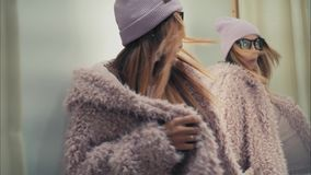 A young stylish hipster female tries on new jacket in the store, dancing and have fun.  Stock Photography