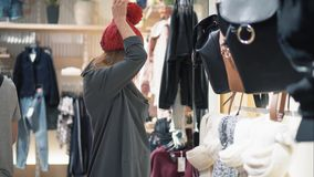 Young stylish hipster female trying on caps in the store and have fun. Shopping.  stock video