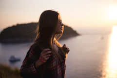 Young stylish hipster girl enjoy sunset on viewpoint. Travel woman with backpack Royalty Free Stock Photo