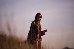 Young stylish hipster girl enjoy sunset on viewpoint. Travel woman with backpack Stock Photo