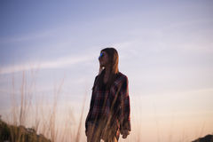 Young stylish hipster girl enjoy sunset on viewpoint. Travel woman with backpack Stock Image