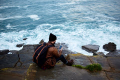 Young stylish hipster guy looking at cell telephone screen while relaxing near sea. Back view of a man traveler with backpack using mobile smart phone while Royalty Free Stock Images
