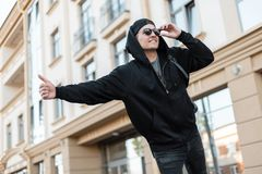 Young stylish hipster man in fashionable black clothes in sunglasses in a cap stands in the city and catches a taxi. Attractive positive guy tourist waiting stock images