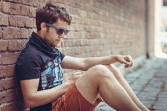 Young stylish hipster man using phone sitting next to a brick wa Stock Images