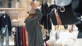 Young stylish hipster woman trying on caps in the store and flirting.  stock footage