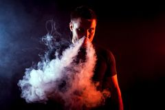 Stylish man smoker. Young stylish male smoker in black T-shirt puffs out of his nose a large cloud of smoke from vape on a black isolated background Royalty Free Stock Images