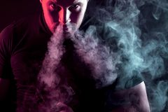 Stylish man smoker. A young stylish male smoker in a black T-shirt stares and exhales from the nose a large cloud of smoke from the vape on a dark isolated Royalty Free Stock Photo