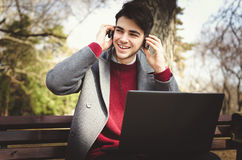 Young stylish male student listening music on headphones with laptop in park. On autumn Stock Image