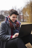 Young stylish male student texting message on laptop in park. On autumn Stock Photos