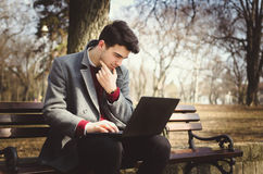 Young stylish male student texting message on laptop. In park on autumn Royalty Free Stock Images