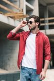 Young stylish man adjusting sunglasses at construction. Building stock images