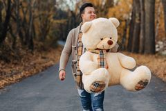 Young man at autumn park road with big bear toy stock photo