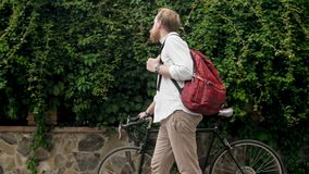 Young stylish man with bag walking with bicycle at park. Stylish man with bag walking with bicycle at park Stock Photos