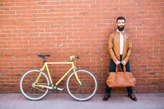 Young stylish man with beard in a brick background standing near the bike with bag in hands stock image