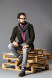 Young stylish man with beard, wearing a jacket sitting on pallets. Young stylish man with a beard, wearing a jacket sitting on pallets royalty free stock images