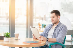 Young stylish man in cafe. Coffee time. Handsome young man in cafe with big window. Man with cup of coffee to go. Man using tablet computer Stock Images