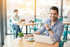 Young stylish man in cafe. Coffee time. Handsome young man in cafe with big window. Man with cup of coffee. Man using laptop, looking at camera and smiling Royalty Free Stock Image