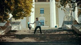 Young stylish man dancing on the stairs on a background of a building. Mid shot stock footage