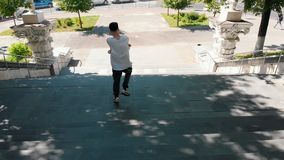Young stylish man dancing on the stairs in daylight stock video