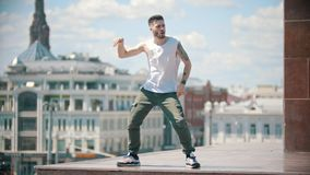 Young stylish man dancing on the stand - centre of the city on the background stock video