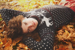Young stylish man dressed in knit sweater with deers lying on au Stock Image