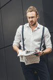 Young stylish man in eyeglasses reading newspaper Royalty Free Stock Image