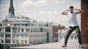 Young stylish man freestyle dancing on the stand - centre of the city on the background. Mid shot stock video footage