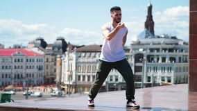 Young stylish man freestyle dancing on the top point in the centre of the city. Mid shot stock footage