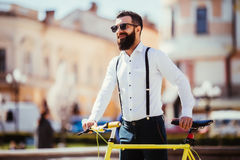 Young stylish man going to work by bike. hipster with a fixie bicycle on the street. bearded man looking away while riding on his Royalty Free Stock Images