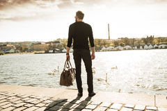 Young stylish man with his bag. Is standing in front of river and looking in the city. Black and white photography stock photo