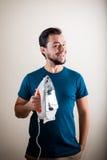 Young stylish man housewife ironing Royalty Free Stock Image