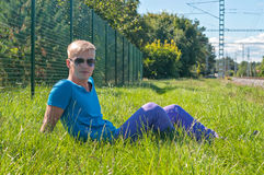 Young stylish man lying on the green grass. Young stylish man an in blue t-shirt lying on the grass Stock Photography