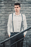 Young stylish man model in classic clothes posing near the brick wall. Fashion shot Royalty Free Stock Images