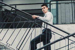 Young stylish man model in classic clothes posing near stairs. Fashion shot Royalty Free Stock Photography