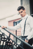 Young stylish man model in classic clothes posing near stairs. Fashion shot Royalty Free Stock Image