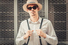 Young stylish man model in hat posing near the cell wall. Fashion shot Stock Image