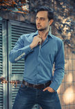 Young stylish man model in jeans and shirt posing in modern park architecture place. Fashion shot. Royalty Free Stock Photos
