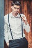 Young stylish man model posing near the wood wall. Fashion shot Royalty Free Stock Photography