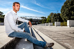 Young stylish man outdoors. Sitting on the steps. A nice Italian man sitting on the steps outside. Blue sky and the Olympic Stadium of Rome (Italy) in the Stock Image