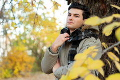 Young stylish man portrait dressed in a jacket and plaid scarf. Royalty Free Stock Photography